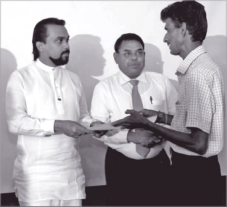 Construction Engineering Services, Housing and Common Amenities Minister Wimal Weerawansa presenting a deed to a tenant.