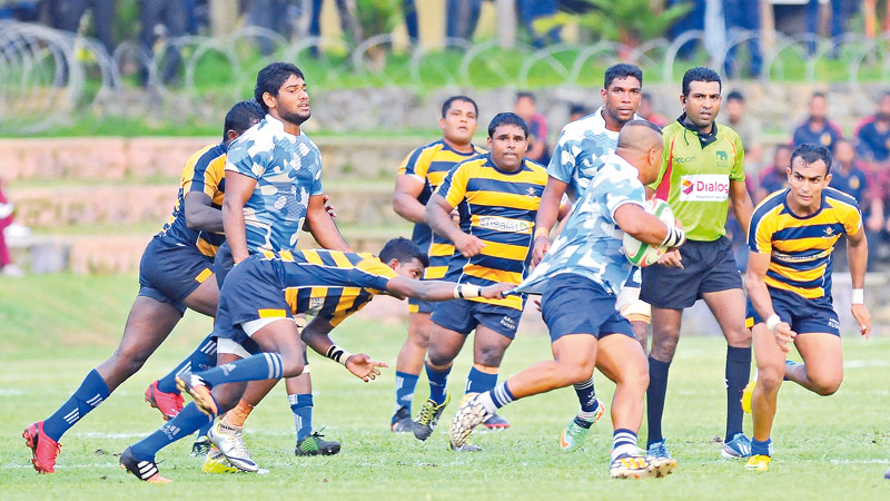 Sri Lanka Navy's Anuranga Walpola makes a break with support from teammate Omalka Gunaratne with two Army players moving across in a bid to foil him in their Dialog 'A' Division League Rugby Match played at Welisara yesterday which Army won 18-17. Picture by Samantha Weerasiri