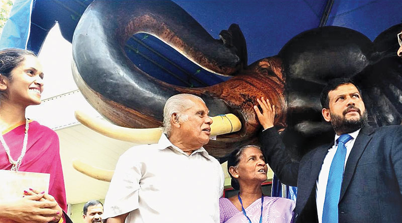 Minister of Industry & Commerce Rishad Bathiudeen stands beside the wooden tusker crafted by H. Wimalarathna of Kelegama, Galle (at centre) and displayed at the show but was promptly purchased by the State Minister of Industry & Commerce Champika Premadasa (far right) paying Rs 1.5 million to the crafts couple.  Picture by Lalith C Gamage