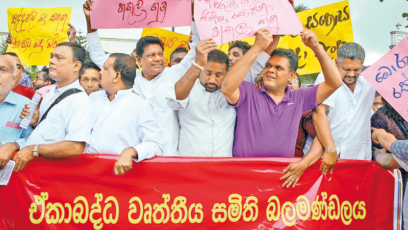 UPFA dissidents yesterday staged a protest opposite the Fort Railway Station against the budget. Picture shows Parliamentarians Kumara Welgama and Rohitha Abeygunawardena holding placards. Picture by Saman Mendis