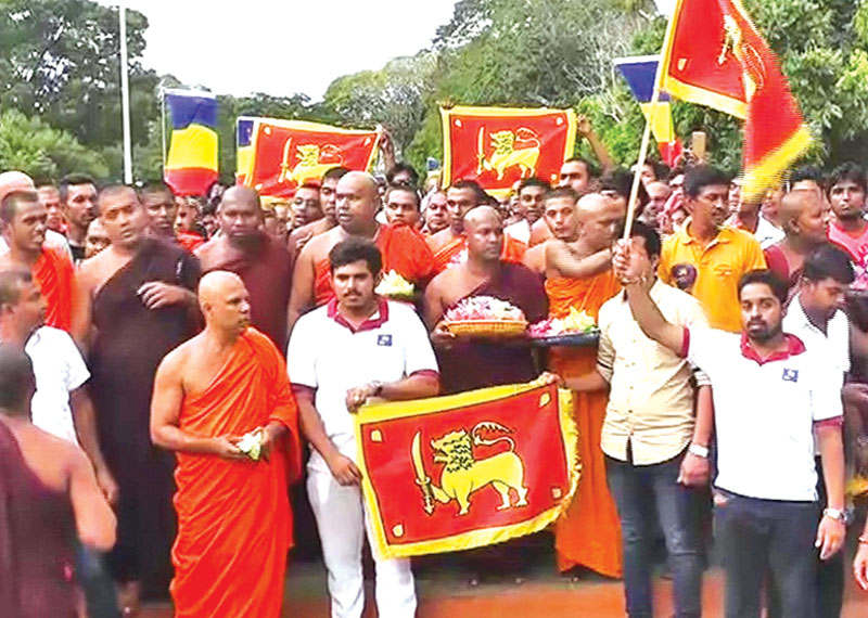 Members of 'Sinha Le' organisation gathered in front of the Dalada Maligawa in Kandy recently to give a special pledge. The 'Sinhale flag' was hoisted at several locations in the Maligawa premises when the organisation members were taking the pledge. Picture by Asela Kuruluwansa