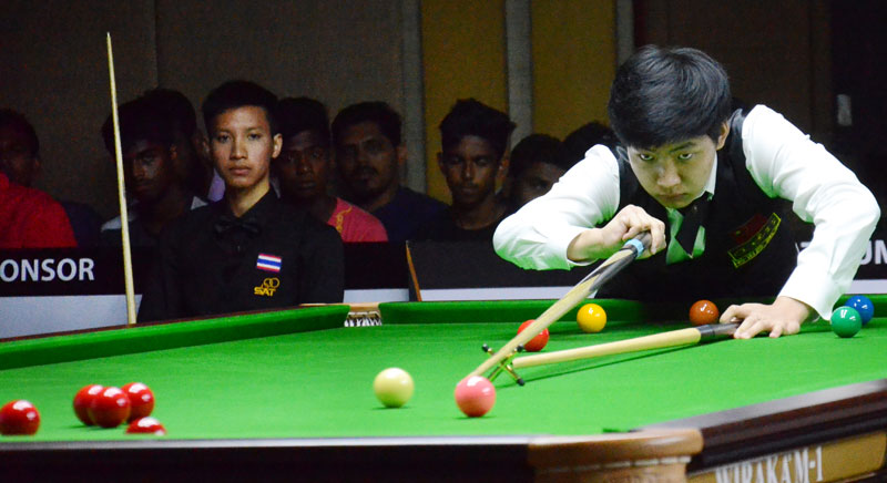 Wang Yuchen of China who became the U-21 Asian Snooker champion plying the final while his opponent, Thailand's R. Yotharuck seated and watching the play. Pictures by Wimal Karunathillaka
