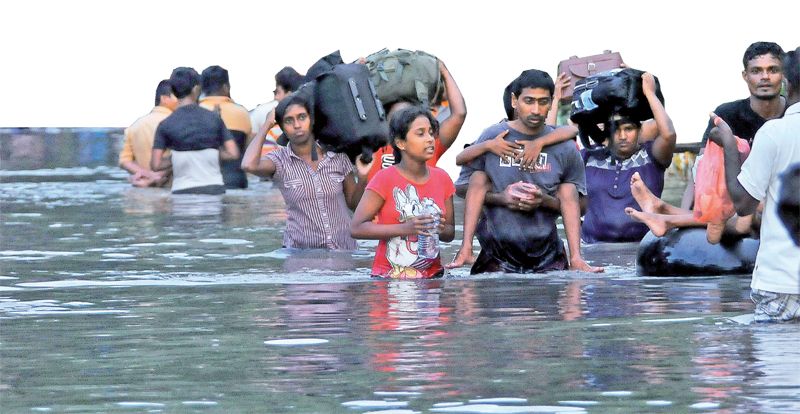 Thousands of people trapped due to floods in low lying areas are seen leaving their homes as water levels  in the Wellampitiya, Kelaniya and Sedawatta areas rose. Boats deployed by Security Forces personnel helped ferry those trapped to safer areas.  Pictures by Rukmal Gamage