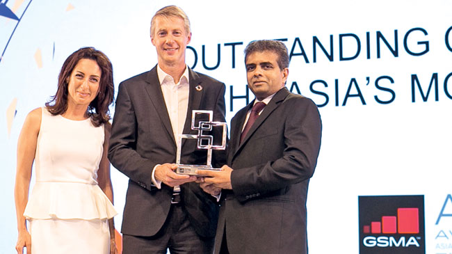 Dr. Hans Wijayasuriya receiving the award from GSMA Director General Mats Granyard.  Mobile World Capital General Manager Therese Jamma looks on.