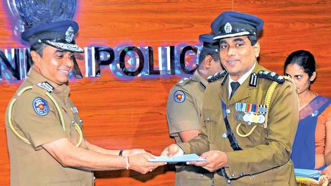 DIG Ajith Rohana receiving his promotion letter from IGP Pujith Jayasundara. Picture by Wasitha Patabendige