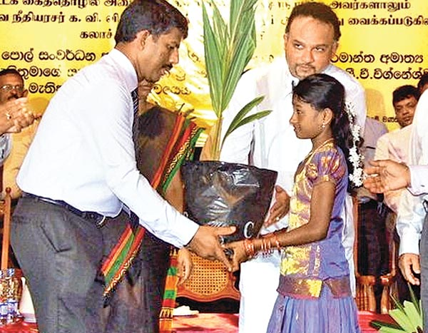 Plantation Industries Minister Navin Dissanayake handing over a coconut plant to participant of the special coconut cultivation programme in the Chavakachcheri Cultural Centre. Picture by Fizel Jabir