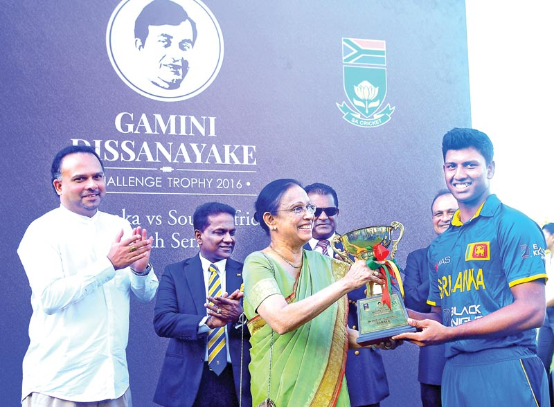 Mrs Shrima Dissanayake, wife of late Gamini Dissanayake hands over the Gamini Dissanayake Trophy to the winning team captain Avishka Fernando. Plantations Minister Naveen Dissanayake and SLC President Thilanga Sumathipala are also present.