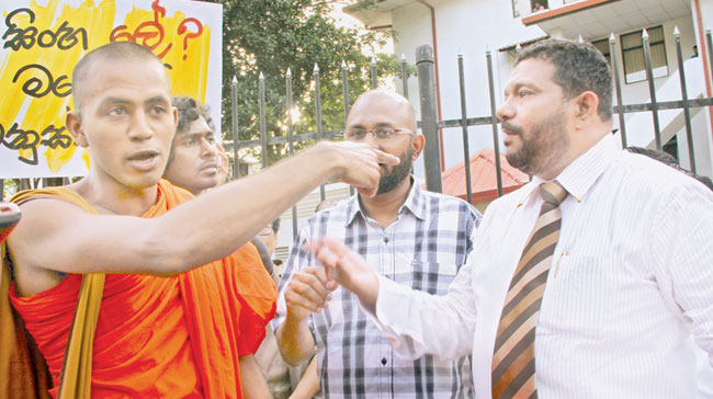 A Thera of the 'Singha Le' organisation and Azad Sallyin trying to make their voices heard. Picture by Mahinda Withanachchi