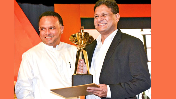 George Steuart  and  Company Chairman Dilith Jayaweera receiving the award from  Plantation Industries Minister Navin Dissanayake.