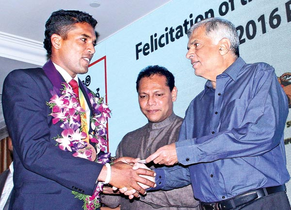 Paralympic medal winner Dinesh Priyantha Herath receives a cheque for Rs. 2.5 million from Prime Minister Ranil Wickremesinghe in the presence of Sports Minister Dayasiri Jayasekera at a special felicitation ceremony organized by Dialog Axiata PLC at Kingsbury Hotel, Colombo last night. Picture by Sudam Gunasinghe