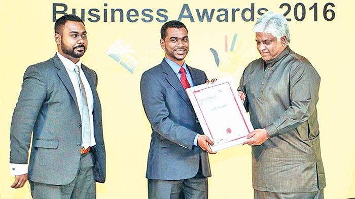 Managing Director of Evolve Technologies Nishantha Pintoe from the Chief Guest Arjuna Ranatunge Minister of Ports and Shipping. Marketing Director of Evolve Technologies Ashan Pintoe  look on.