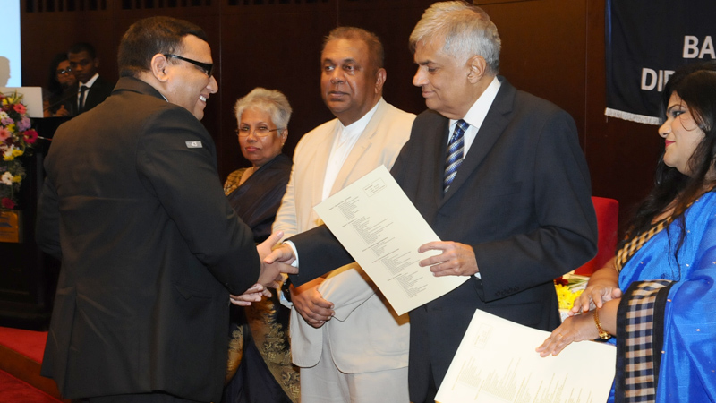 Prime Minister Ranil Wickremesinghe presenting a certificate to a student at the annual convocation of the Bandaranaike International Diplomatic Training Institute (BIDT) at the BMICH. Looking on is Foreign Affairs Minister Mangala Samaraweera.