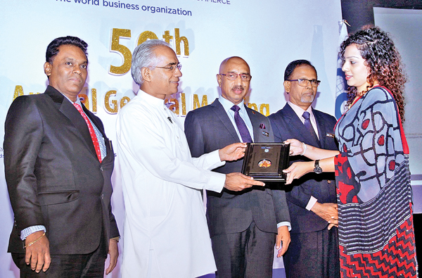Deputy Minister Eran Wickramaratne presenting an award at the event. Chairman, ICC, Keerthi Gunawardane, Chairman Education Comitte, Lal Jayawardane look on. Picutre by Saliya Rupasinghe