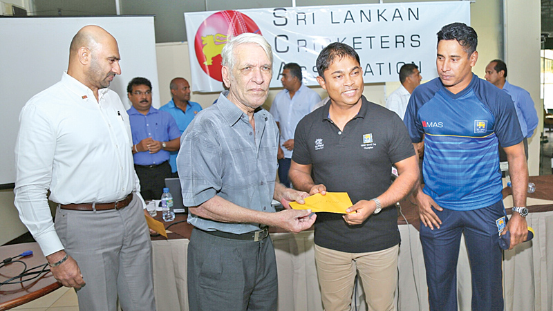Former Sri Lanka wicket-keeper/batsman Russell Hamer one of the first beneficiaries of the SLCA Benevolent Fund receives a cheque from Romesh Kaluwitharana, member of the 1996 World Cup winning team at the SSC pavilion yesterday. Former SLCA president Graeme Labrooy and Chaminda Vaas, member of the 1996 World Cup winning team are also present. (Pic by Rukmal Gamage)