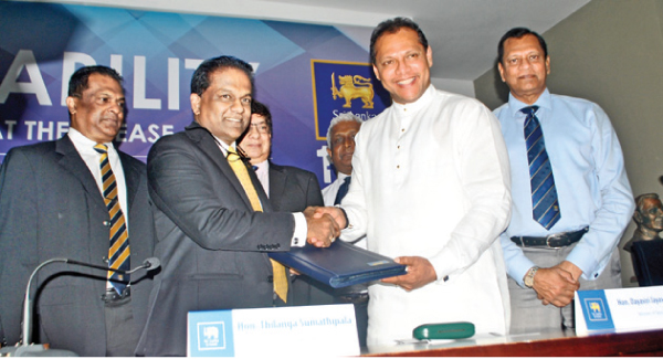 SLC president Thilanga Sumathipala handing over last year's financial reports of SLC to Sports Minister Dayasiri Jayasekara at the Sports Ministry auditorium yesterday. SLC secretary Mohan de Silva, its treasurer Shammi Silva and SLC Financial Advisory Committee chairman Nuski Mohomed are also present. Picture by Ranjith Asanka