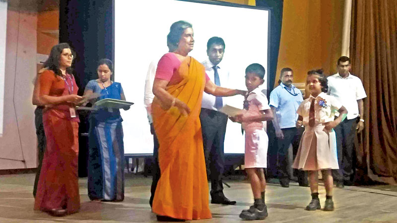 Former President Chandrika Kumaratunga distributing prizes and certificates  among winners of an inter school paintings competition