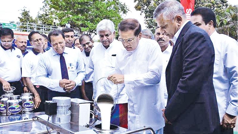 President Maithripala Sirisena opened the integrated Kotmale Milk Dairy plant at Minuwangoda yesterday to intensify their manufacturing capabilities. Cargills Deputy Chairman Ranjit Page and officials look on while President Sirisena pours fresh milk into the container. Pictures by Sudath Malaweera.