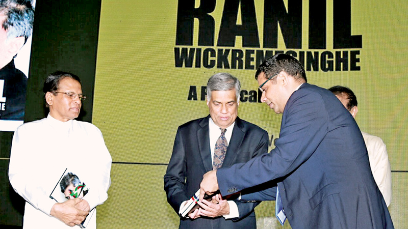 The launch of the book 'Ranil Wickremesinghe-A Political Biography,' was held at the BMICH last Tuesday. Here, the writer Dinesh Weerakkody presenting a copy of the book to Prime Minister Ranil Wickremesinghe as President Maithripala Sirisena and Speaker Karu Jayasuriya look on.  Pictures by Malan Karunaratne