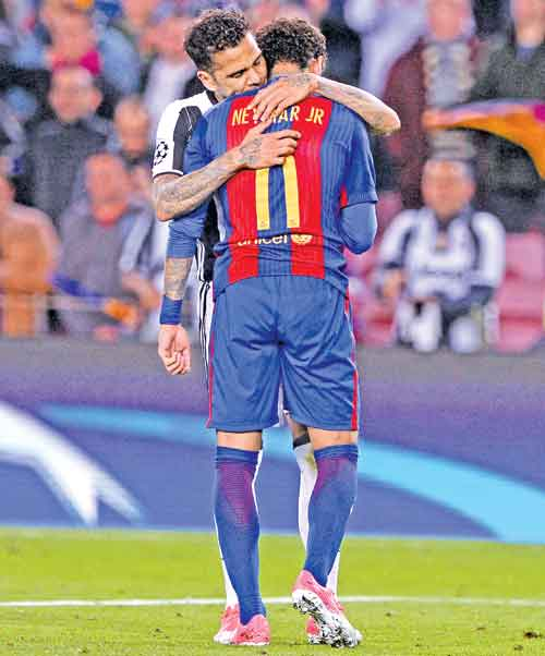 Barcelona's Brazilian forward Neymar (R) is comforted by Juventus' Brazilian defender Dani Alves after their disqualification by Juventus at the end of the UEFA Champions League quarter-final second leg football match. -AFP