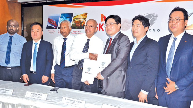 Micro Holdings Chairman Dr. Lawrence Perera exchanging the agreement with SK Group Senior Vice President C. H. Lee while officals look on after inking the partnership. Picture by Vipula Amarasinghe