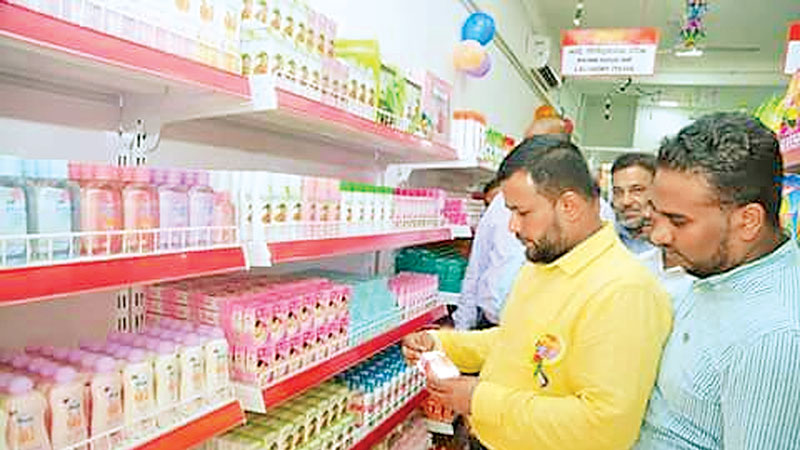 Trade and Commerce Minister Rishad Bathiudeen inspecting some items displayed at the 380th Sathosa branch at Pottuvil.