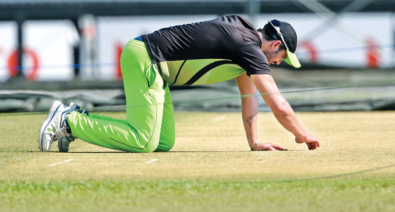 Zimbabwe captain Graeme Cremer has a closer look at the Galle International Stadium pitch that is being prepared for today's first ODI against Sri Lanka. AFP pic by Ishara Kodikara