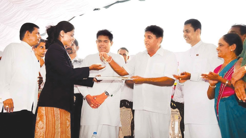 Nadeeka Lakmali receiving the keys of the house together with related documents from Minister Sajith Premadasa. Minister Gayantha Karunathilake and Galle district parliamentarians Wijepala Hettiarachchi and Bandulal Bandarigoda are also present. Picture by Mahinda P. Liyanage- Galle Central Special Corr.