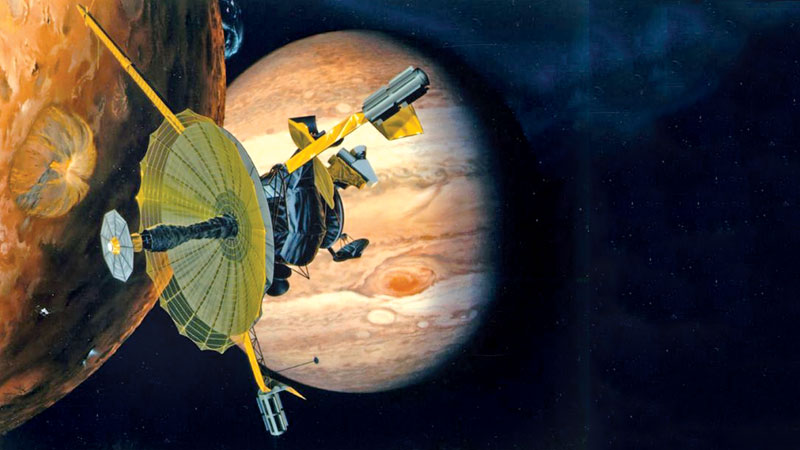This NASA artist's concept shows the Galileo spacecraft flying by Jupiter's volcanic moon Io (L) and the gigantic planet.- AFP