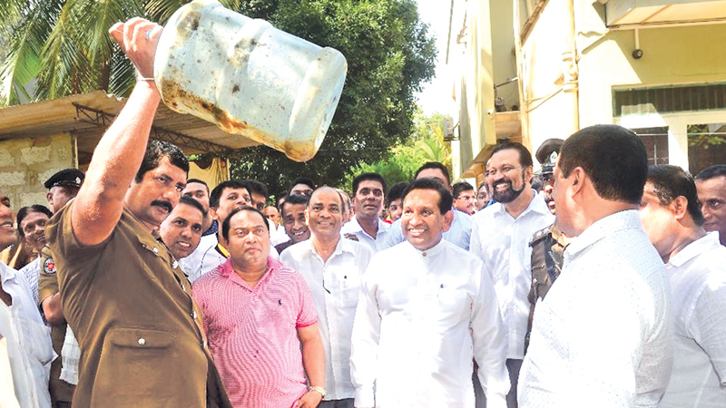 Health Workers and WHO officials showing some of the receptacles detected with mosquito larvae to Health and Indigenous Medicine Minister Dr. Rajitha Senaratne at the launching of the dengue eradication drive in China Fort, Beruwala yesterday.