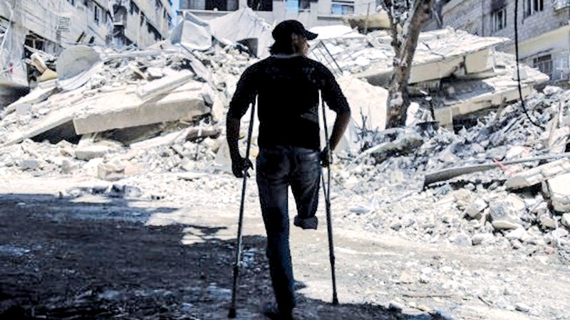 A Syrian man uses crutches to walk near a building that was  destroyed following a reported air strike on the rebel-held town of Ayn  Tarma, in Syria's eastern Ghouta area Saturday.- AFP