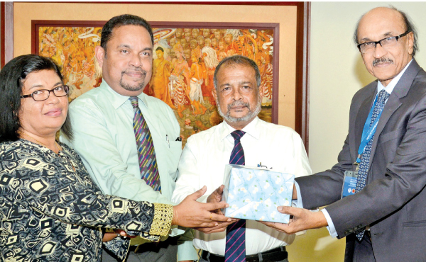 Bangladesh Bank Governor Fazle Kabir presenting a token of appreciation to Pan Asia Bank's Director/Chief Executive Officer Nimal Tillekeratne. AGM Operations and Credit Administration Harsha Kurukulasuriya and Acting Manager Central Operations, Dilrukshi Guruge and are also present