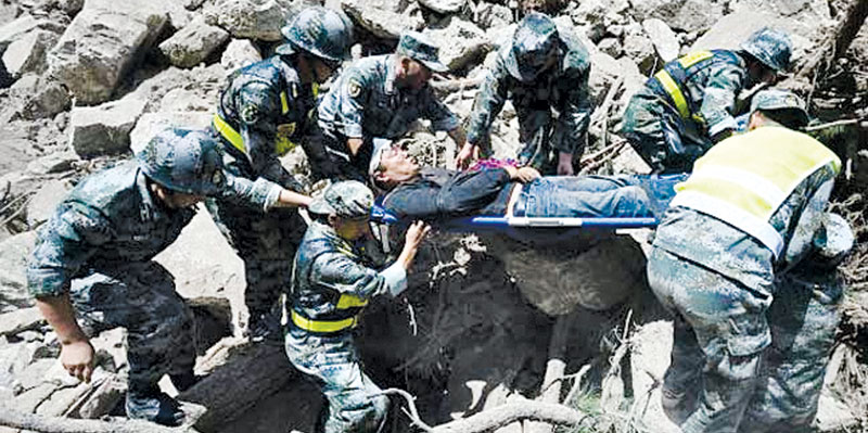 Rescue workers carry a survivor.