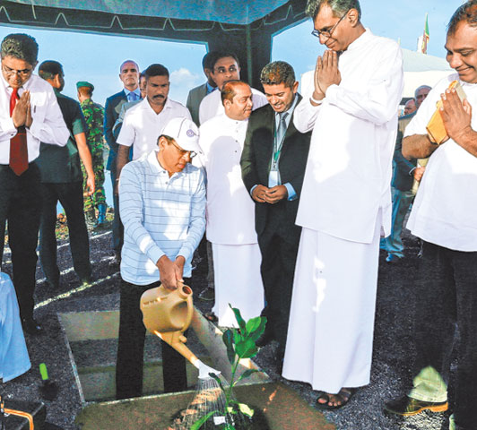 President Maithripala Sirisena watering a plant at the Karadiyana waste management project inauguration.