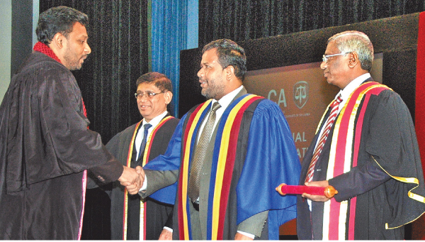 Minister of Industry and Commerce Rishad Bathiudeen  congratulating a certified Chartered Accountant at the CASL 2017 Convocation joined by CASL President Lasantha Wickremasinghe at BMICH on  September 12.