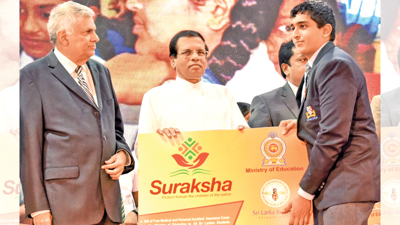 President Maithripala Sirisena and Prime Minister Ranil Wickremesinghe yesterday handed over token certificates of the Suraksha Health Insurance Scheme to students at the official launch of the scheme held at Temple Trees. Picture by Sudath Silva