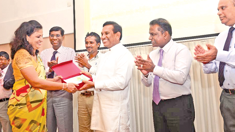 Health Minister Dr. Rajitha Senaratne hands over an award. Deputy speaker Thilanga Sumathipala and Health Ministry officials look on.