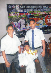 Karathe Gold medalist D.L. Pidum Dewnila is  seen here with his coach D. Nishantha (left) and chief instructor R.K.A. Dinesh. Picture by Kalutara Central Special H.L. Sunil Shantha