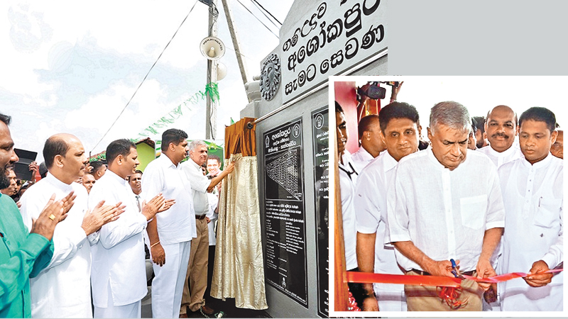 Prime Minister Ranil Wickremesinghe unveiling the plaque to open the 'Ashokapura' housing project in Maningala, Nattandiya yesterday. Housing Minister Sajith Premadasa looks on. Pictures by Hirantha Gunathilake