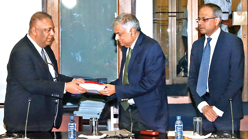 The National Action Plan for the Protection and Promotion of Human Rights 2017–2021 was launched at the Parliament Complex yesterday. Picture shows Finance and Media Minister Mangala Samaraweera presenting the first copy of the report to Prime Minister Ranil Wickremesinghe. Law and Order and Southern Development Minister Sagala Ratnayaka was also present. Picture courtesy Prime Minister's Media Unit