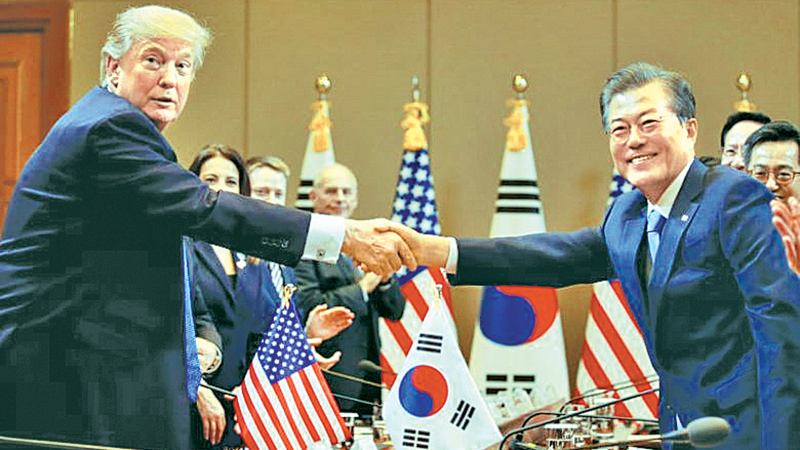 US President Donald Trump and South Korea's President Moon Jae In shake hands before the summit meeting at the Presidential Blue House in Seoul yesterday. - AFP
