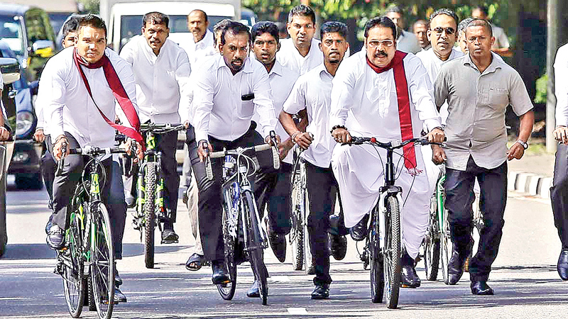 Former President Mahinda Rajapaksa coming to Parliament on a pushbike along with Joint Opposition members. Picture by Rukmal Gamage