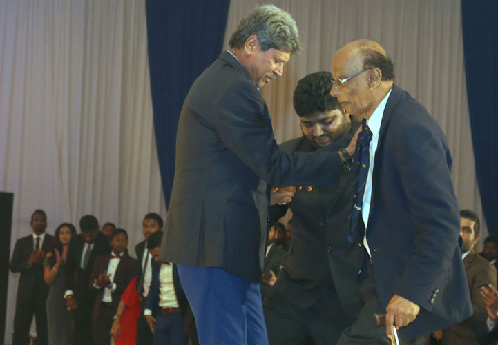 Neil Perera is helped onto the stage by former Indian World Cup winning captain Kapil Dev who was guest of honour at the Dialog annual awards night held at Waters Edge.