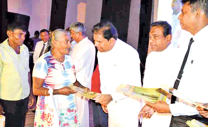 Lands and Parliamentary Reforms minister Gayantha Karunathilake handing over a deed. Picture by Mahinda P.Liyanage, Galle Central Special Corr
