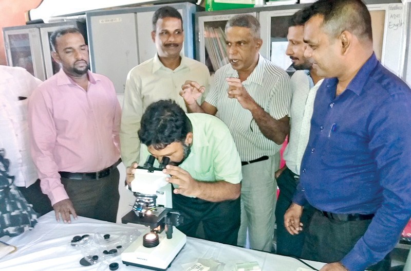 Assistant Education Director (Science) M. M. A. Wahid explaining how to use microscopes to teachers. Picture by I. L. M. RIZAN, Addalaichenai Central Corr.