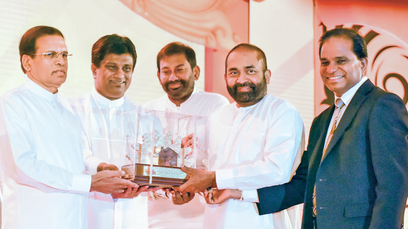 President Maithripala Sirisena unveiled the next phase of the Soorya Bala Sangramaya (Battle for Solar Power) national programme at a ceremony held at Waters' Edge yesterday. Picture shows President Maithripala Sirisena being presented with a token of appreciation by Power and Energy  Minister Ranjith Siyabalapitiya, Deputy Minister Ajith P. Perera, Primary Industries Minister Daya Gamage and Ministry Secretary B.M.S. Batagoda on the occasion. Picture by  Chandana Perera (See page 7)