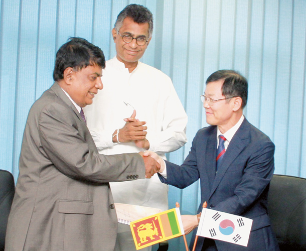 Megapolis and Western Development Ministry Secretary Nihal Rupasinghe and SenYoung Company Vice President Kim Nam Siyol  exchanging documents after signing the MOU at the Ministry premises in the presence of Megapolis and Western Development Minister Patali Champika Ranawaka. Picture by Kelum Liyanage