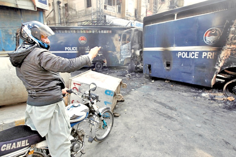 A passerby photographs police prison vans destroyed during clashes with protesters near the Faizabad junction in Islamabad.