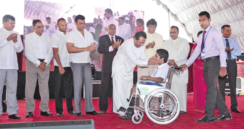 Minister S. B. Dissanayake presenting a wheelchair to a differently-abled person.