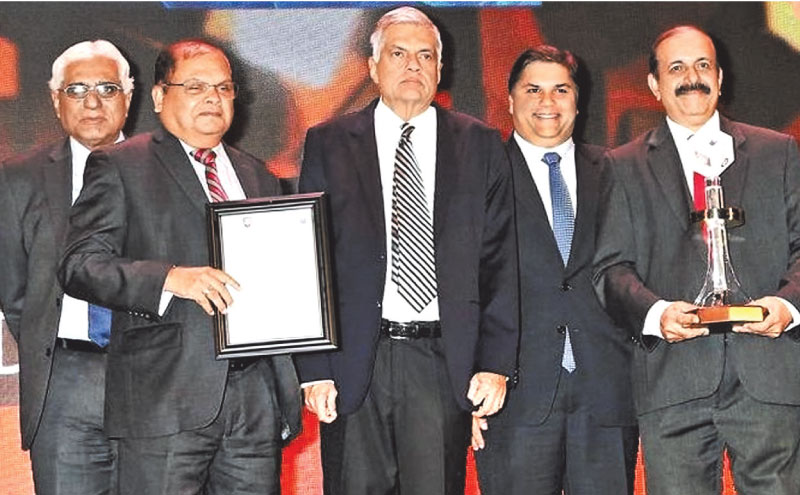 Commercial Bank Chairman Dharma Dheerasinghe and Deputy Chairman M.P. Jayawardena after receiving the overall award from Prime Minister Ranil Wickremesinghe. Central Bank Governor Dr Indrajit Coomaraswamy  looks on.
