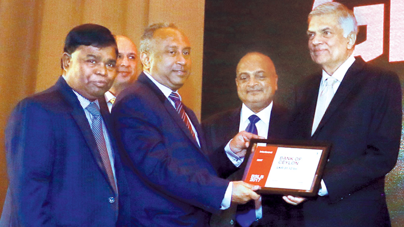 The Bank of Ceylon secured the first place at the awards ceremony for Sri Lankan brands sponsored by the international Interbrand rating group held at Hilton Hotel yesterday. BoC Chairman Ronald C. Perera PC receives the award from Prime Minister Ranil Wickremesinghe. BoC General Manager D.M. Gunasekera and Daily FT Editor Nisthar Cassim were present. Picture by Hirantha Gunathilake